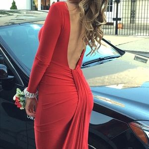 Red long sleeve gown with open back and train